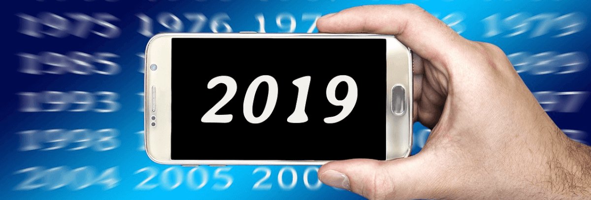 Image of a hand holding a cellphone against a calendar graphic. On the phone is the year 2019.