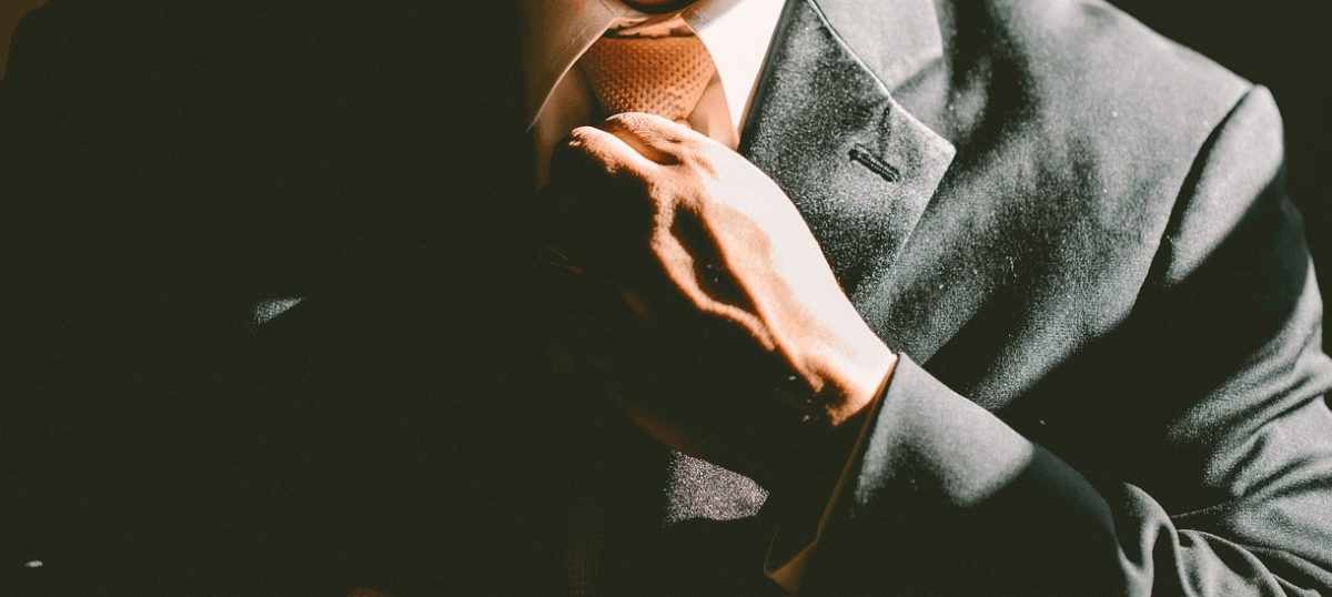 Image of a man adjusting his suit