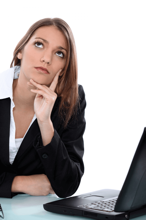 Picture of a woman in business attire considering her options in front of a computer.
