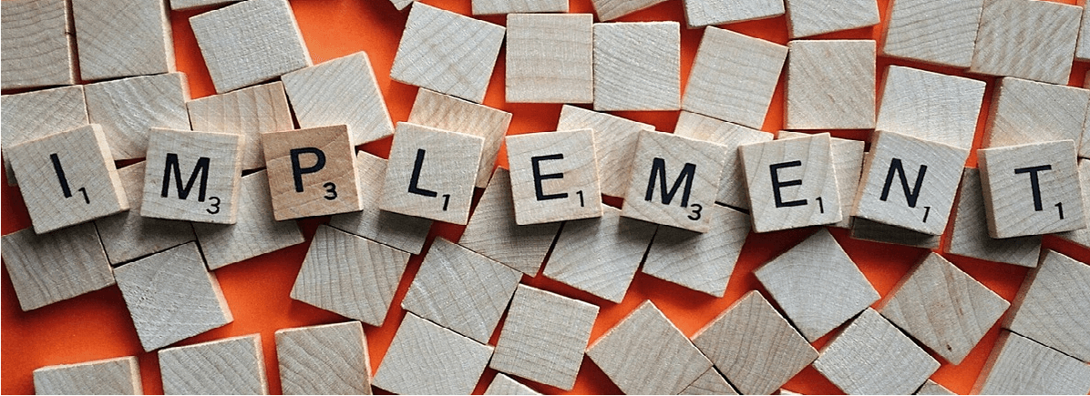 """Image of scrabble game pieces spelling the word """"Implement"""""""