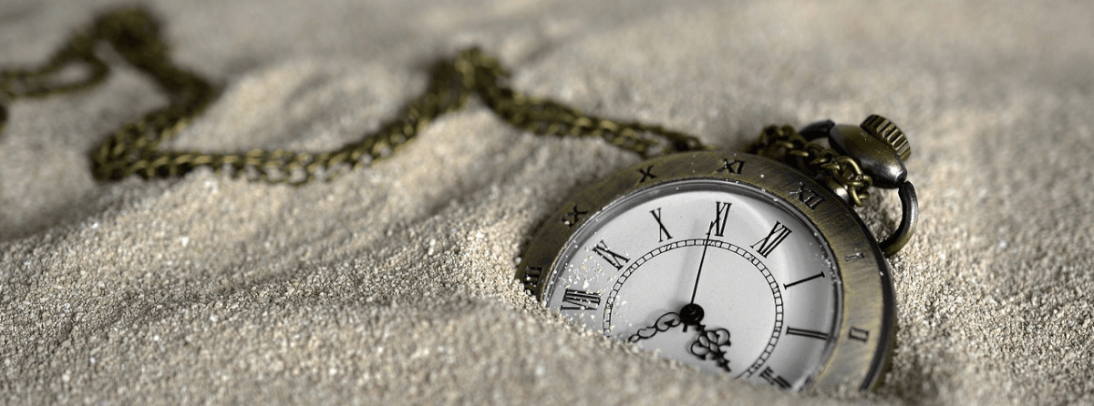 Image of a watch half-buried in sand